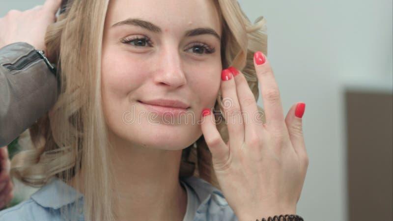 Reflexão da jovem mulher de sorriso com cabelo louro no espelho do salão de beleza que tem o cabelo denominado fotografia de stock