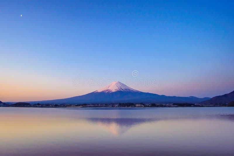 A reflexão da montanha de Fuji com neve tampou e a lua no nascer do sol da manhã no kawaguchiko do lago, Yamanashi, Japão fotografia de stock royalty free