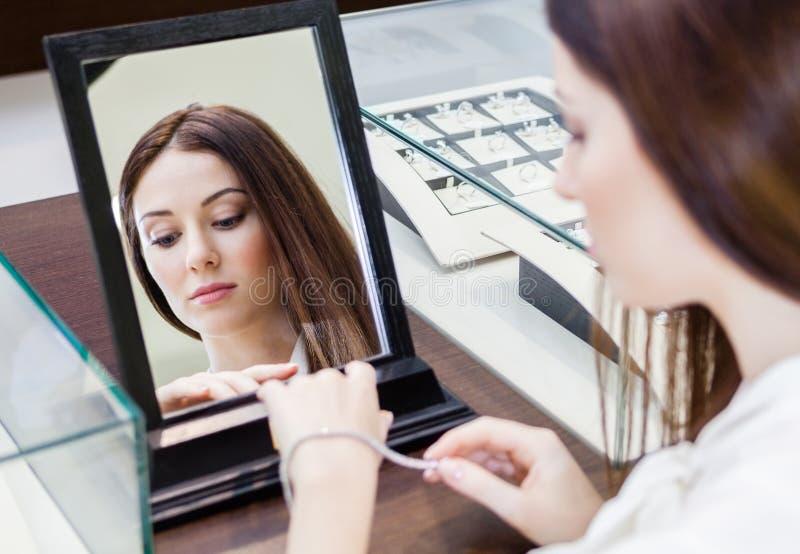 Reflexão da mulher que tenta no bracelete foto de stock