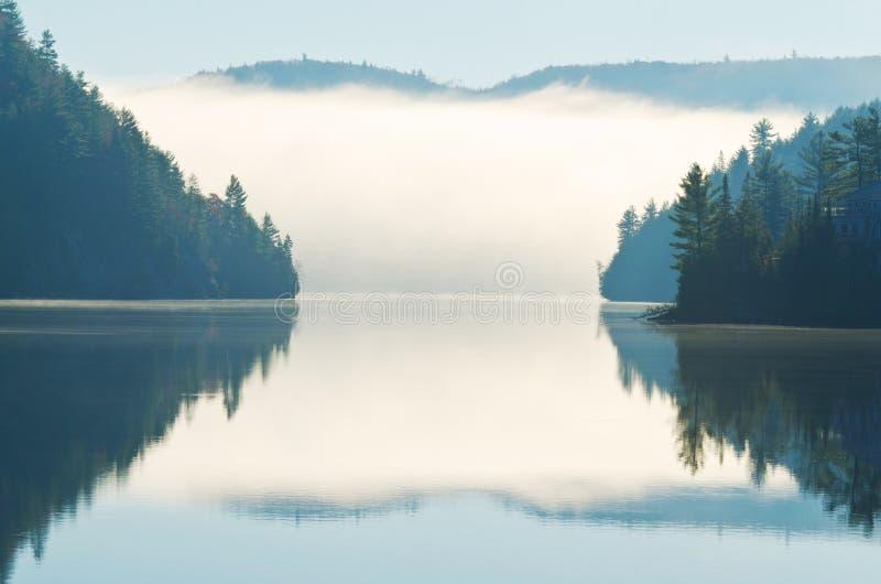 Reflexão da névoa da manhã que aumenta no lago fotos de stock royalty free