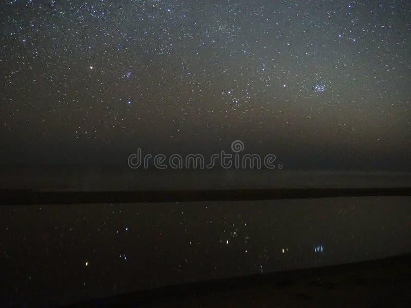 Reflexão das estrelas do céu noturno, constelação de Orion Pleiades e do Touro sobre o mar fotografia de stock royalty free