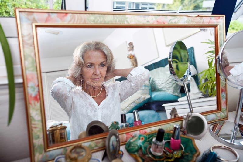 Reflexão de espelho da mulher superior que põe sobre a colar em casa imagens de stock