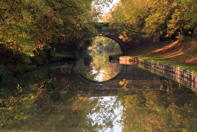 Reflexão de espelho de árvores da ponte e do outono Arched no canal grande da união imagens de stock royalty free