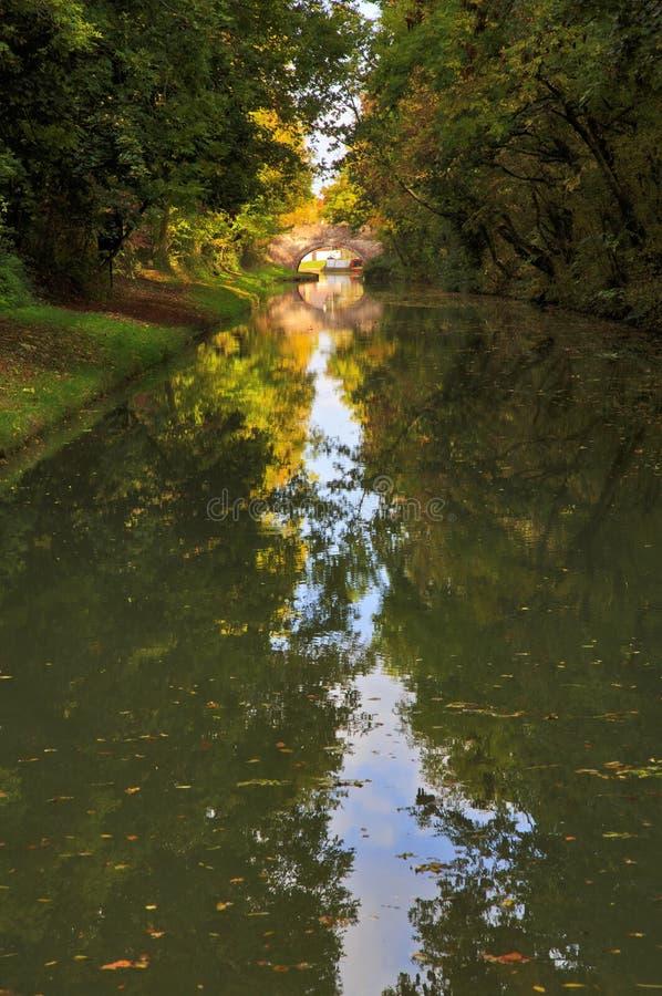 Reflexão de espelho de árvores da ponte e do outono Arched no canal grande da união fotografia de stock