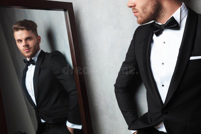Reflexão de espelho do homem novo relaxado que veste um smoking preto foto de stock royalty free