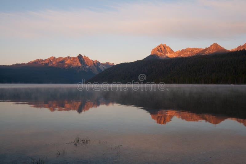 Reflexão de montanhas do Sawtooth no nascer do sol no lago redfish, Idaho fotos de stock royalty free