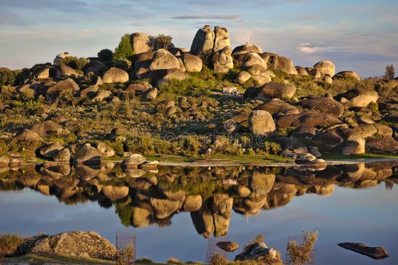 Reflexão de pedras grandes sobre um lago em Los Barruecos, Espanha fotos de stock royalty free