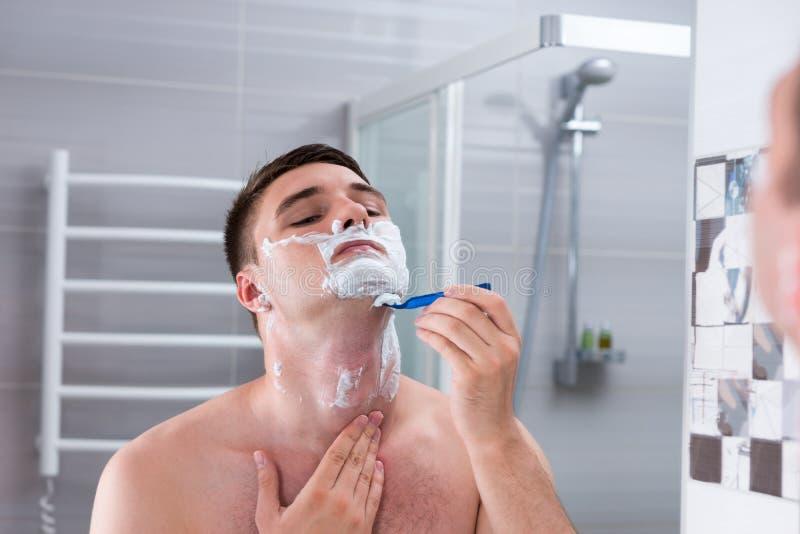 Reflexão de um homem que barbeia sua caixa com um razer no espelho imagens de stock royalty free