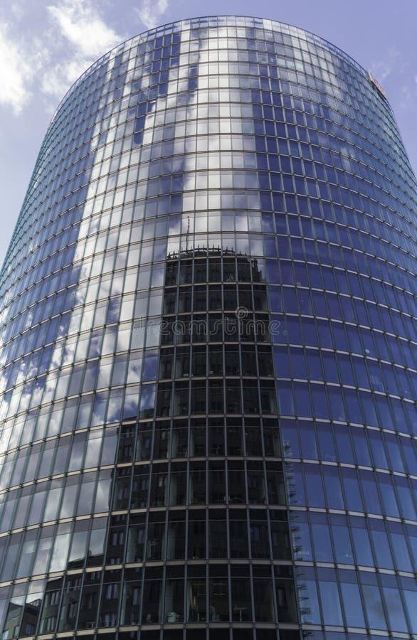 Reflexão de uma construção nas janelas de vidro de um arranha-céus e de nuvens imagem de stock royalty free