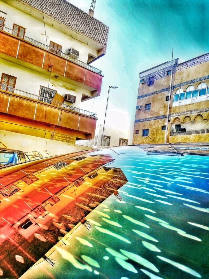 A reflexão de uma construção velha e do céu no carro de vidro fotos de stock