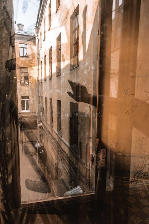 Reflexão de uma mão em uma janela que olha no pátio fotos de stock royalty free