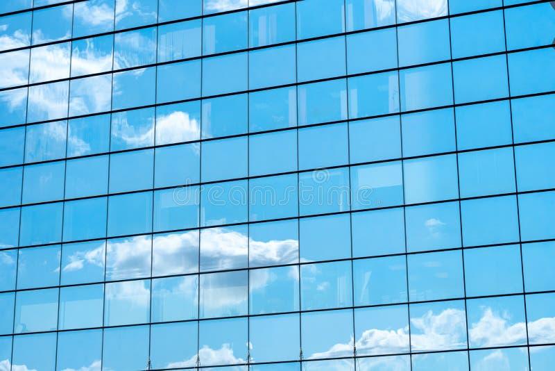 Reflexão do céu azul e das nuvens na parede do espelho da construção da cidade imagem de stock