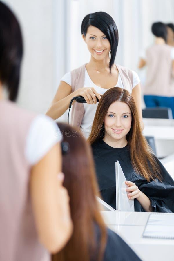 Reflexão do cabeleireiro que faz o corte de cabelo para a mulher fotografia de stock royalty free