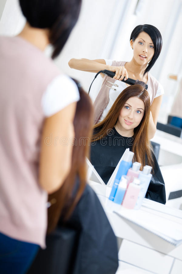 Reflexão do cabeleireiro que faz o penteado para a mulher fotografia de stock royalty free