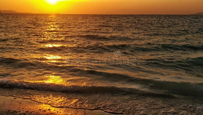 Reflexão do crepúsculo sobre as ondas pequenas que atacam à praia fotografia de stock royalty free