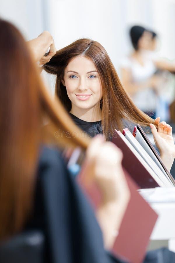 Reflexão do esteticista que faz o penteado para a mulher imagem de stock