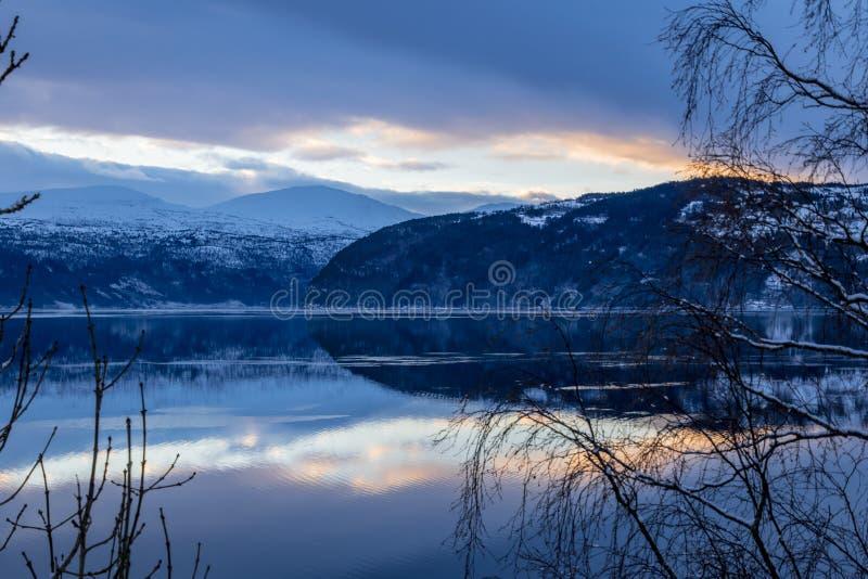 Reflexão do por do sol e das montanhas no lago fotografia de stock