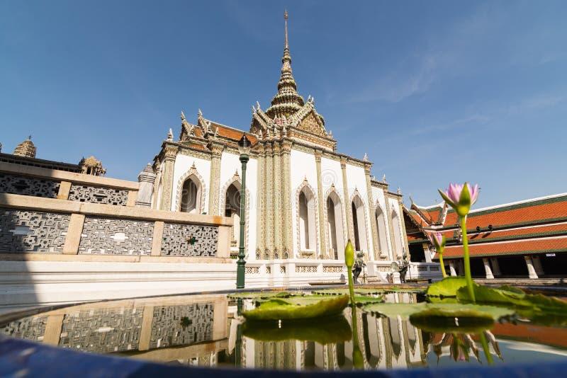 Reflexão do templo de Phra Viharn Yod em uma lagoa com a flor de lótus no complexo grande do palácio em Banguecoque, Tailândi foto de stock royalty free