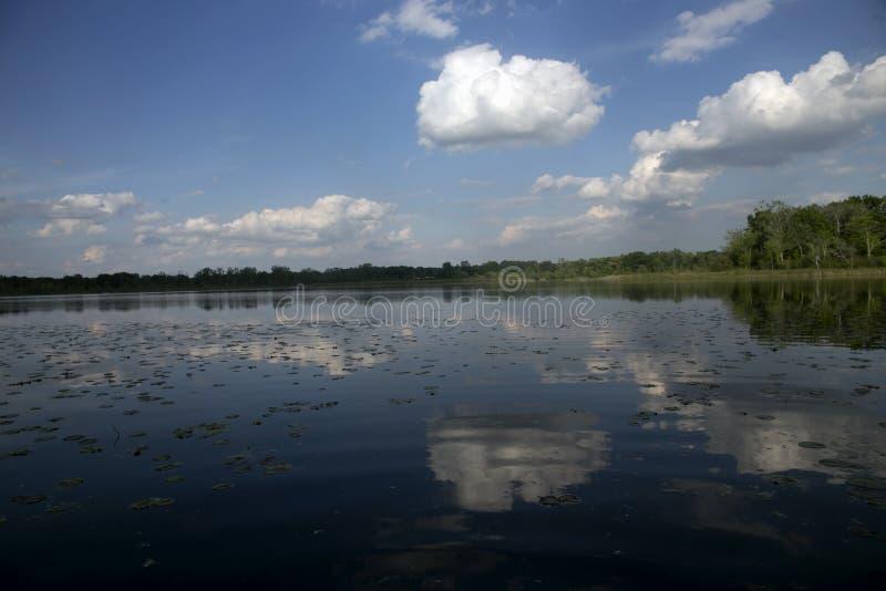 Reflexão do verão das nuvens em um lago em Michigan imagem de stock
