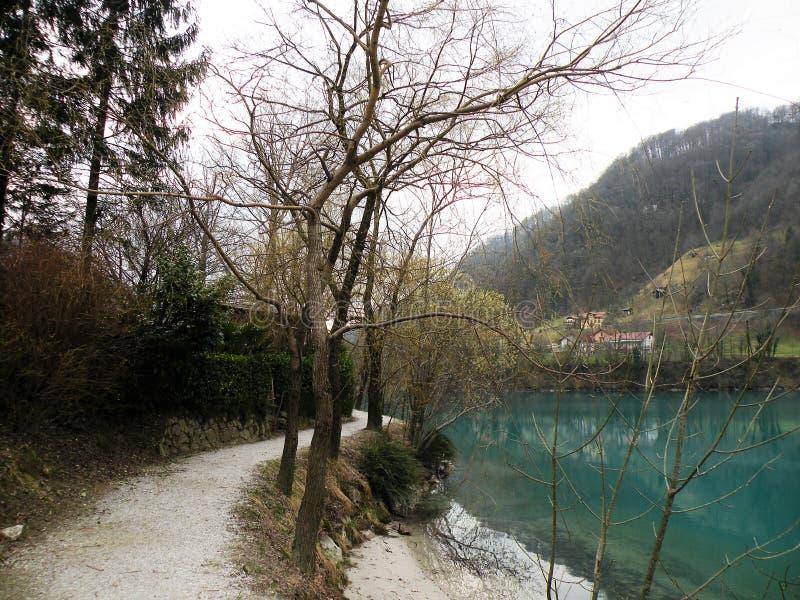 Reflexão dos montes, das montanhas, da vila e do céu na água do turquise imagem de stock