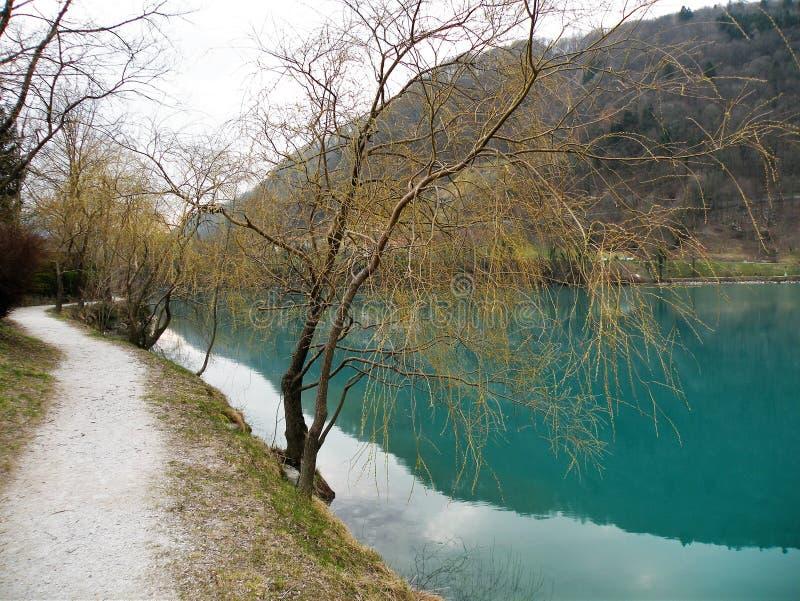 Reflexão dos montes e a vila e o céu na água do turquise fotografia de stock royalty free