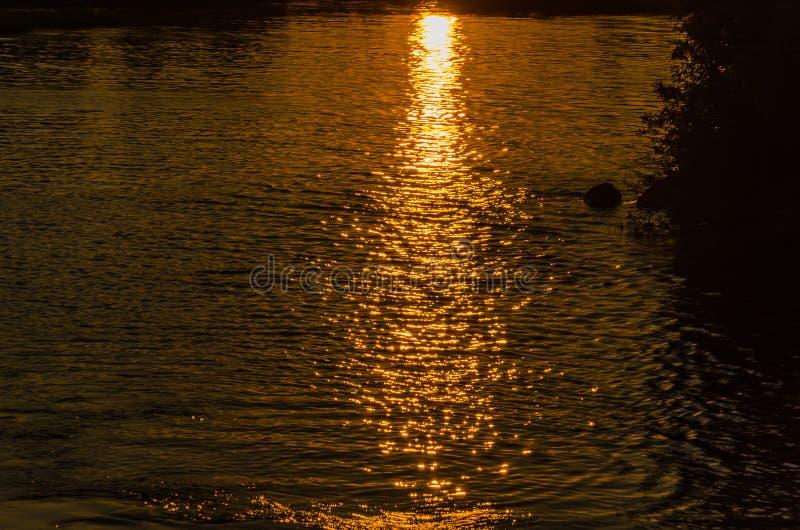 Reflexão dos raios do sol de ajuste na superfície da água Textura da ?gua Fundo natural imagens de stock royalty free
