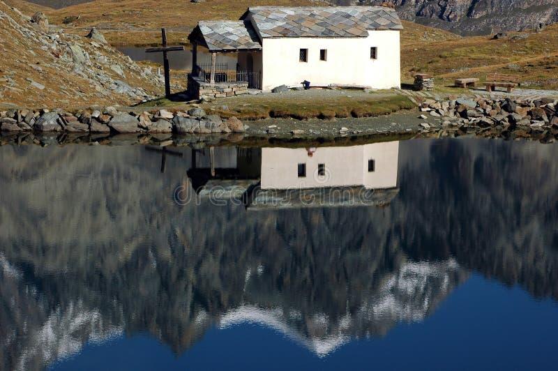 Reflexão em uma capela pelo lago fotografia de stock