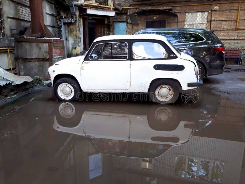 Reflexão em uma poça de um carro velho em um pátio arruinado foto de stock royalty free