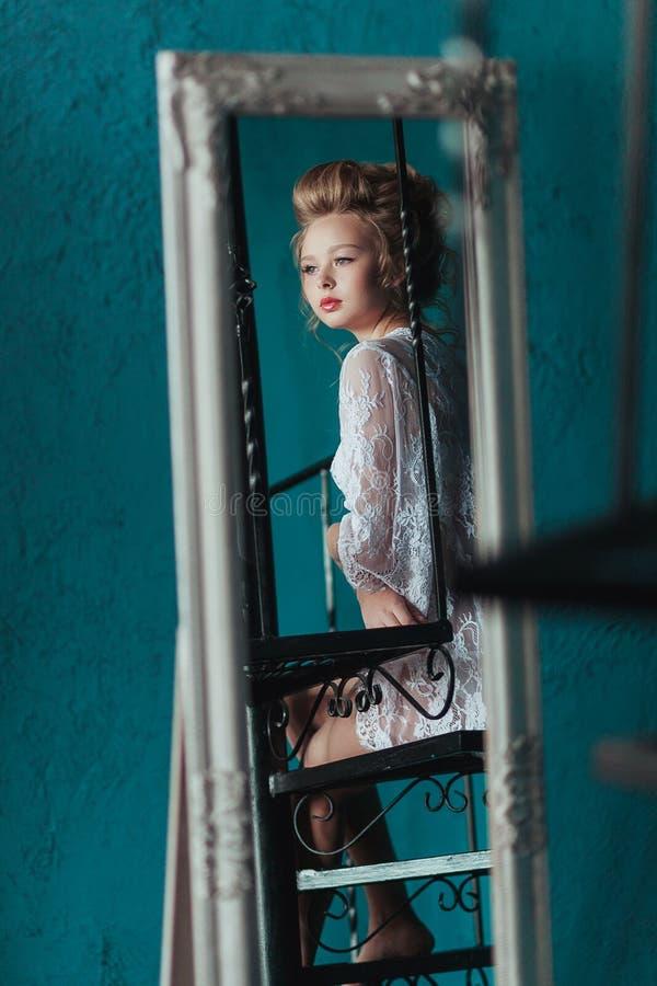 Reflexão na noiva loura bonita modesta do espelho no négligé branco que senta-se nas escadas pretas do ferro forjado imagens de stock royalty free