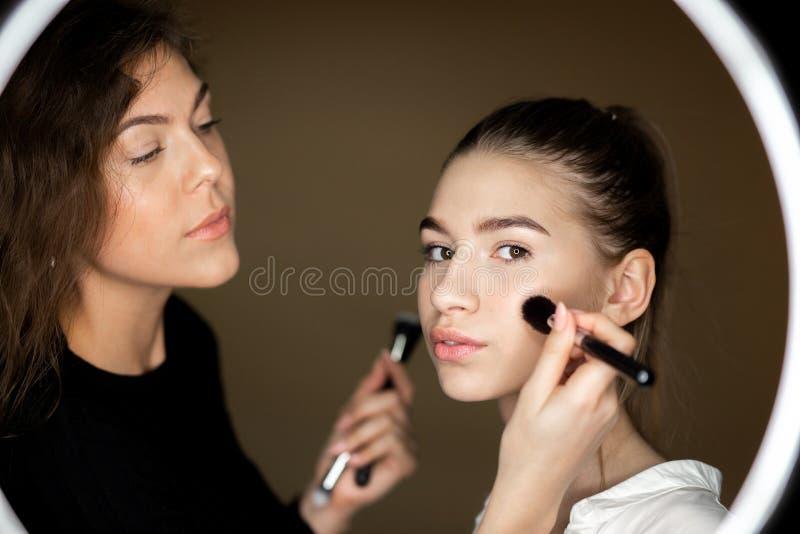 A reflexão no espelho do maquilhador a menina encantador está fazendo a composição a uma moça bonita imagem de stock