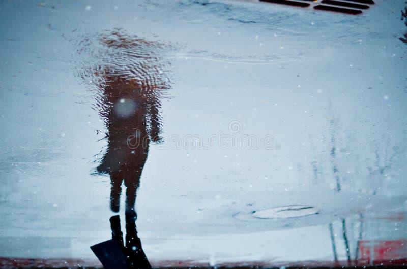 Reflex?o obscura em uma po?a apenas da pessoa de passeio na rua molhada da cidade durante a chuva e a neve Conceito do humor foto de stock