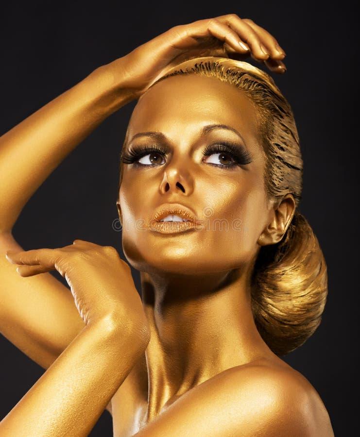 Reflexão. Retrato da mulher lustrosa com composição dourada brilhante. O bronze Bodypaint fotografia de stock