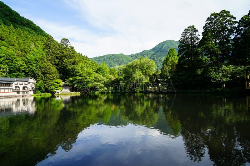 Reflexão simétrica da paisagem verde natural abundante bonita da montanha no lago fresco Kinrin com fundo do céu azul fotografia de stock