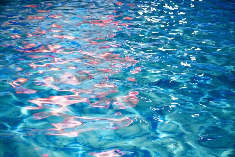 Reflexão vívida das luzes vermelhas na superfície ondulada da água azul fotografia de stock royalty free