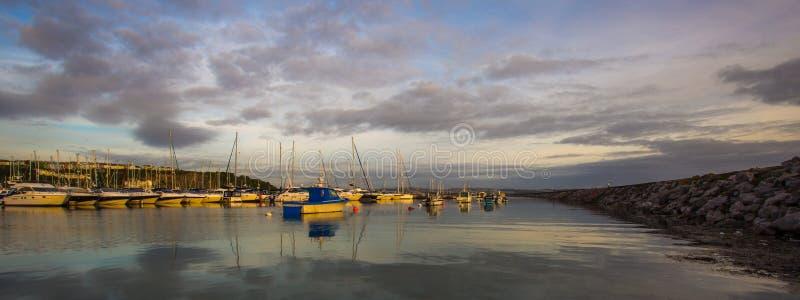 Reflexões da água do nascer do sol da cidade da costa imagem de stock