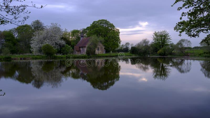 Reflexões da igreja de St Leonard em Hartley Mauditt Pond, penas sul parque nacional, Reino Unido fotos de stock