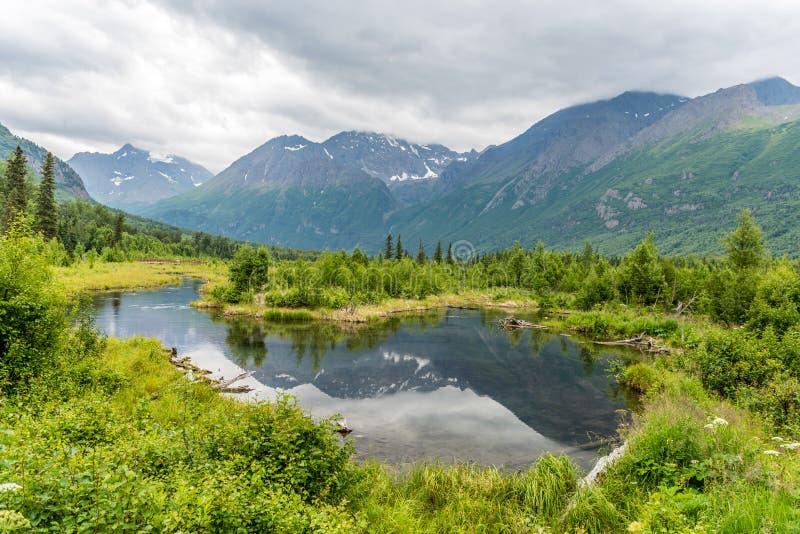 Reflexões da montanha de Chugach no ` s Eagle River de Alaska foto de stock