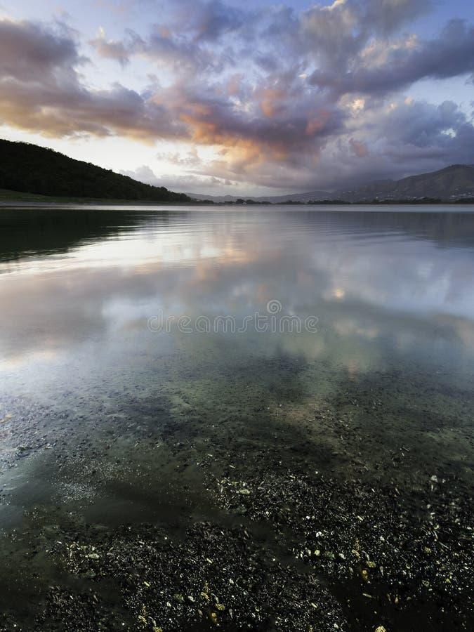 Reflexões da nuvem do por do sol sobre um lago tranquilo imagens de stock