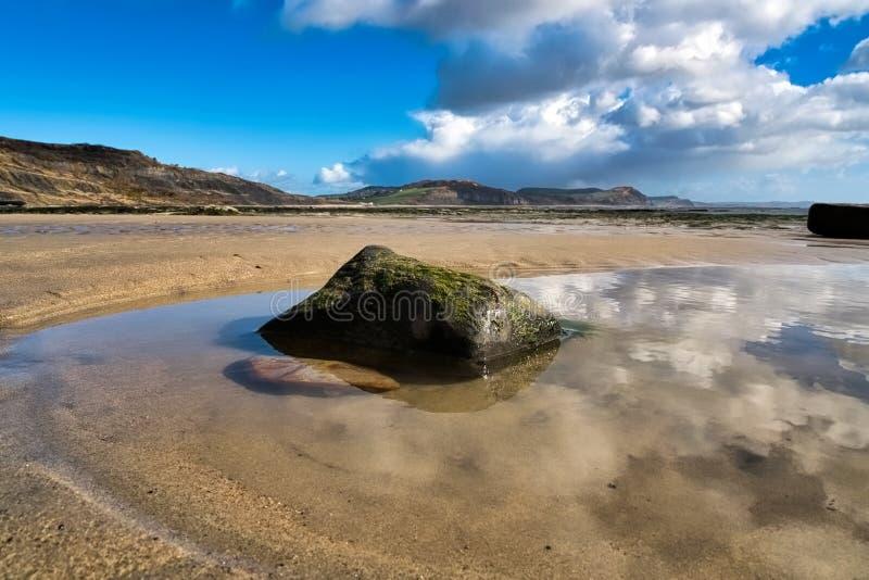 Reflexões da nuvem na praia do leste - Lyme Regis fotografia de stock