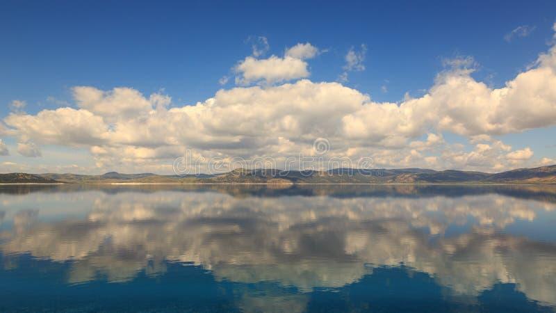 Reflexões das nuvens e da montanha no lago Salda em Turquia imagem de stock