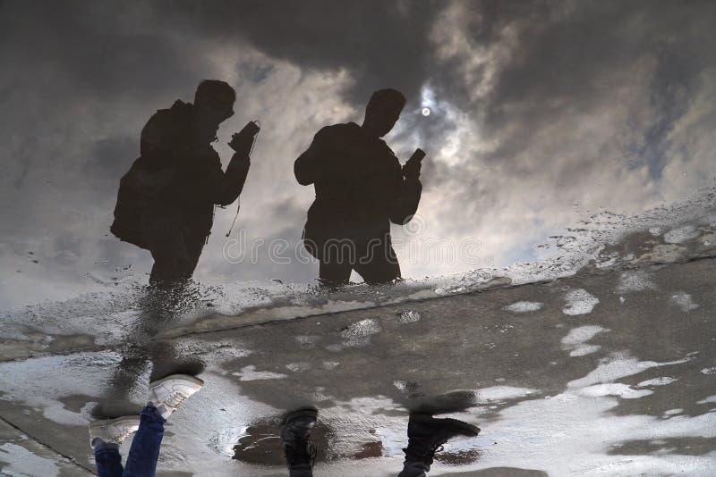 Reflexões de dois homens na água fotografia de stock royalty free