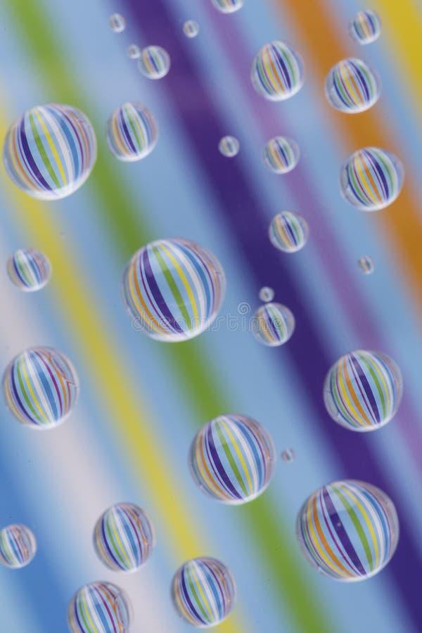 Reflexões de papel listrado em gotas pequenas múltiplas da água fotos de stock royalty free