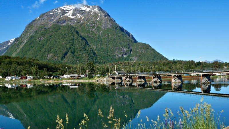 Reflexões de uma bela montanha com neve e uma ponte sobre um rio foto de stock