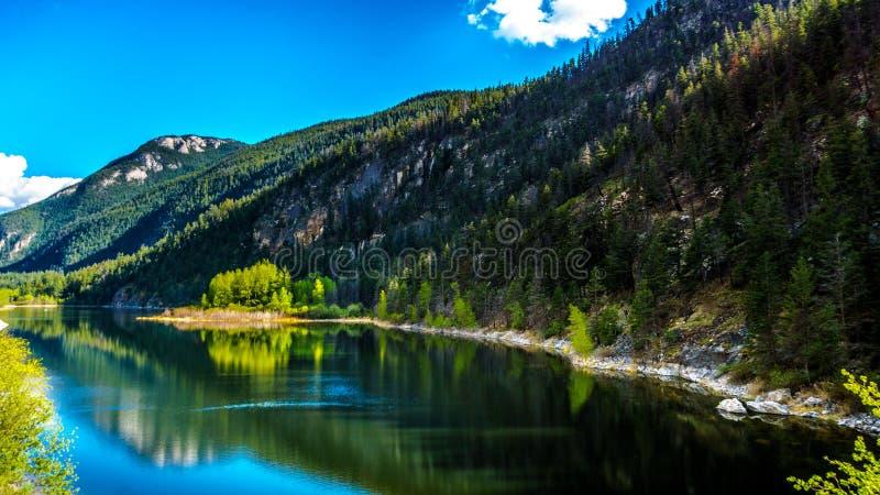 Reflexões do céu azul, das árvores e das montanhas na superfície lisa na água claro do lago crown fotografia de stock royalty free