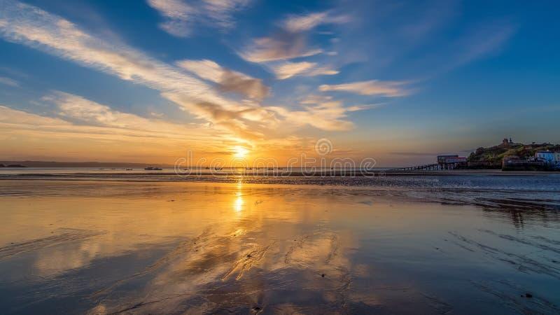 Reflexões do nascer do sol na maré baixa em Tenby em Gales imagens de stock