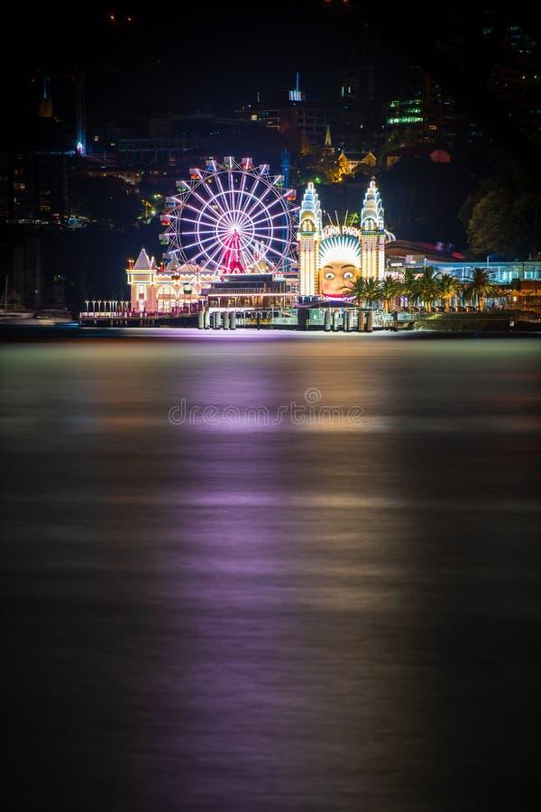 Reflexões do parque temático de Luna Park na noite através de Sydney Harbour imagem de stock royalty free