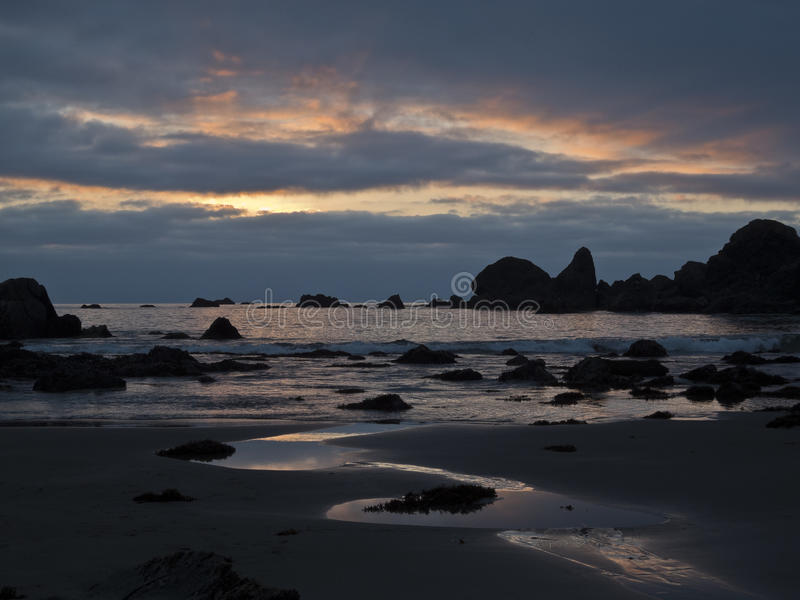 Reflexões do por do sol na praia de Harris imagens de stock