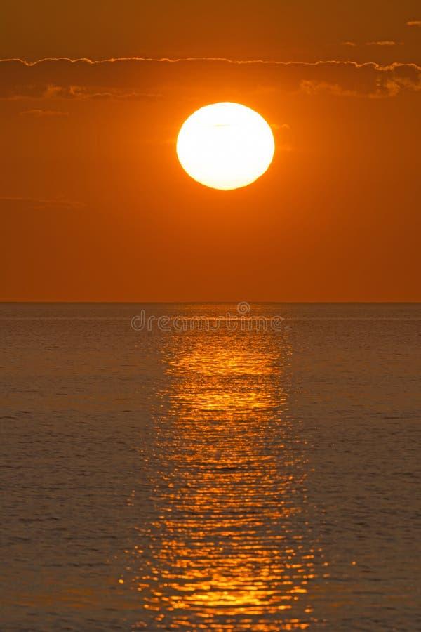 Reflexões do por do sol sobre uma baía do oceano imagens de stock royalty free