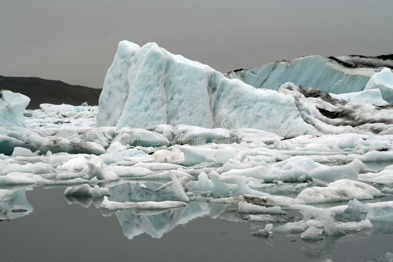 Reflexões dos icerbergs azuis e brancos de cristal na água escura preta na luz sombrio não ofuscante - geleira de Jökulsárlón Jok imagem de stock