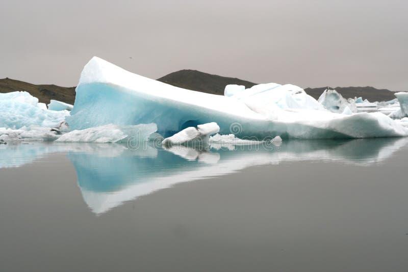 Reflexões dos icerbergs azuis e brancos de cristal na água escura preta na luz sombrio não ofuscante imagens de stock royalty free